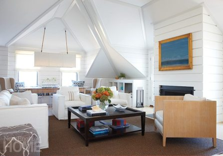 """The living areas are on the second floor of the """"upside-down"""" house, where the interesting angles and pinched corners reflect the exterior roof planes. Horizontal shiplap walls give the cottage an appropriately maritime feel."""