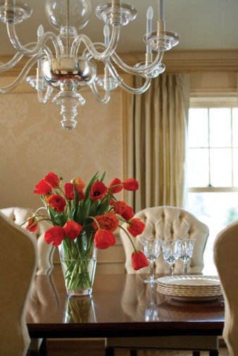Classic and modern elements mingle in the dining room chandelier. The dining chairs wear an easy-to-clean Sunbrella velvet.