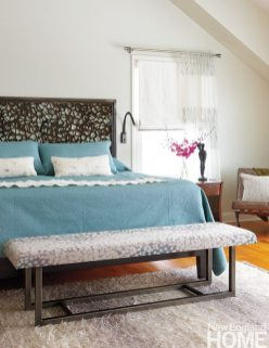 """""""Every room should have a surprise,"""" says designer Joyce Clear. The master bedroom has several, from its unique headboard to its steel bench covered in Donghia fabric to the seafoam hue of the bedding."""