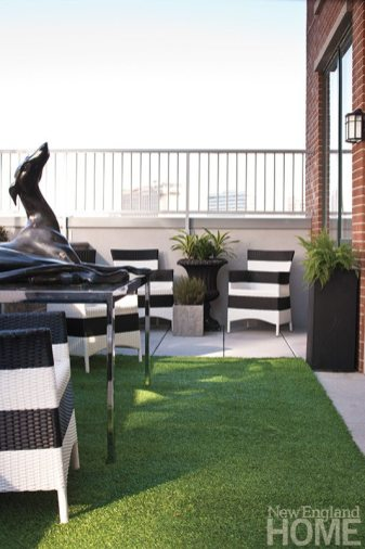 A carpet of faux grass gives the terrace its garden appeal. The striped chairs are from Terrain in Westport.