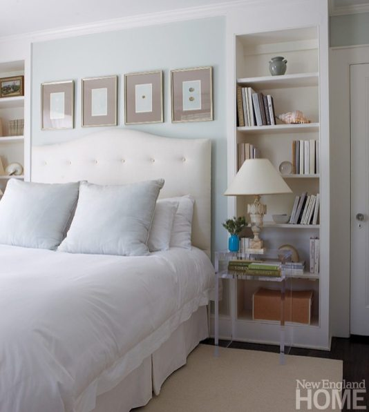 The master bedroom carries out the designer's serene design scheme with pale-blue walls, white bedding, Lucite bedside tables and symmetrical bookcases.
