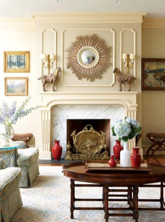 """The living room'€™s stylish grasscloth wallcovering has a subtle silvery sheen that makes it a perfect backdrop for everything from the Greek key-€""""patterned sofa pillows to the moldings and fluted mantel to the chic coffee table with its faux bamboo base."""