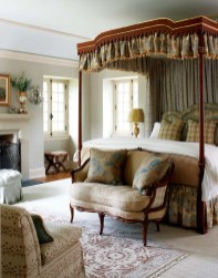 A sweet settee sits at the foot of the elegant bed with its gilded canopy.