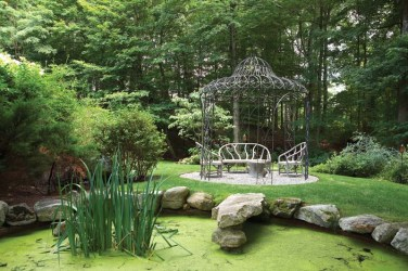 The gazebo holds faux bois concrete furnishings.