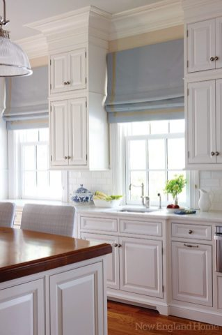 Roman shades bring color to the pale kitchen.