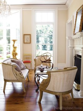A living room sitting area is outfitted with swan-armed chairs and settee upholstered in cream-colored velvet and trimmed with nailheads.