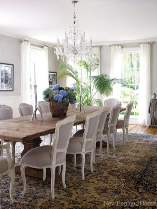 The rustic dining table gets dressed up with nineteenth-century Louis XV–style chairs upholstered in gray linen. A Chinese rug and voile curtains contribute to the lush ambience.