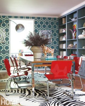 """David Hicks wallpaper sets the mood in the dining room, where, instead of a chandelier, a """"hair-dryer"""" lamp illuminates the vintage table that sits on hide rugs."""