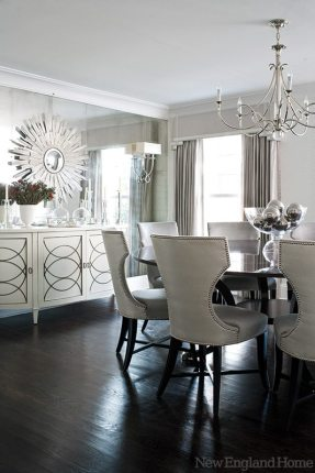 The dining room's silvery hues shimmer in numerous reflective surfaces, including an entire wall covered in antique mirror. The homeowners entertain frequently, so a large round table was of utmost importance to offer plenty of seating for guests and help ease the flow of conversation.