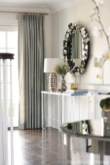 Contemporary accessories complement the foyer's classic herringbone-pattern wood floor.