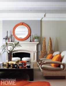 High-gloss white woodwork pops against walls of two shades of gray in the living room, while accessories in brilliant orange add an energetic vibe.