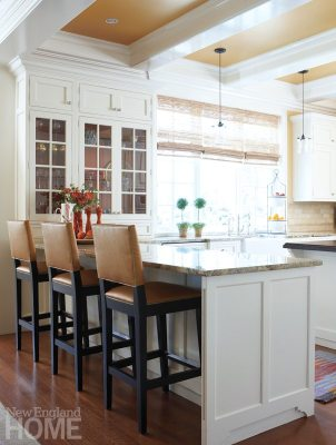 Orange makes its way into the bright kitchen, with bold swipes of the hue on the ceiling.