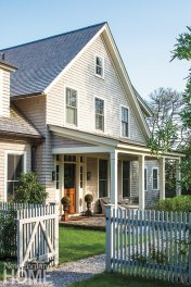 """A picket fence with climbing roses and a covered front porch provide the story-book look author Jane Green wanted for her """"new old house."""""""
