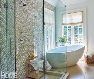 The master bath incorporates a sculptural tub and limestone floor.