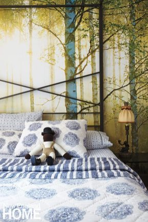 A woodland-scene wallpaper behind the bed brightens and enlarges the space.