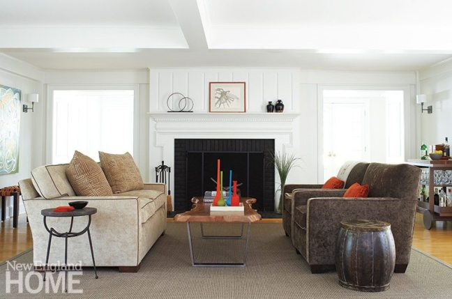 "The living room's large fireplace threatened to overpower the living room, so Kalur used her signature ""chic neutrals"" to scale back its imposing size."