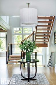 The dramatic, open staircase of iron and oak seems to float in its airy, light-filled, glass-enclosed stairwell.