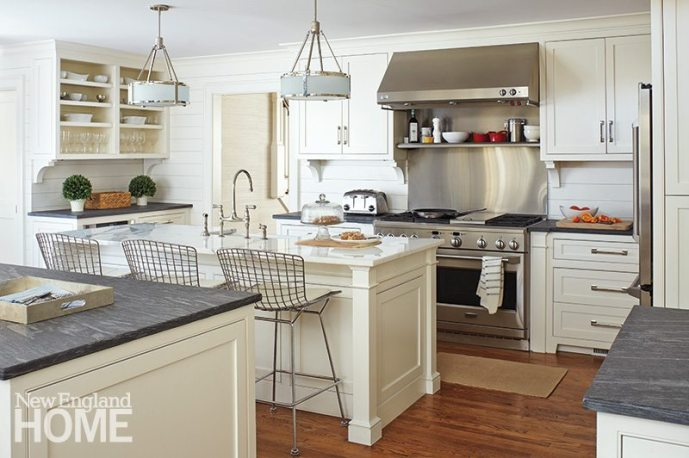 Original wood floors in the kitchen were sanded and stained. Nickel hardware complements the stainless-steel appliances and basket-chair barstools.