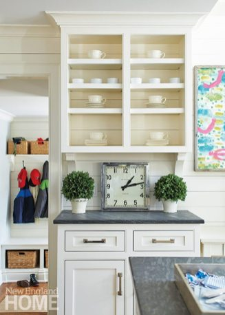Limestone counters add interest to the simple white cabinetry with its mix of open and closed shelving.