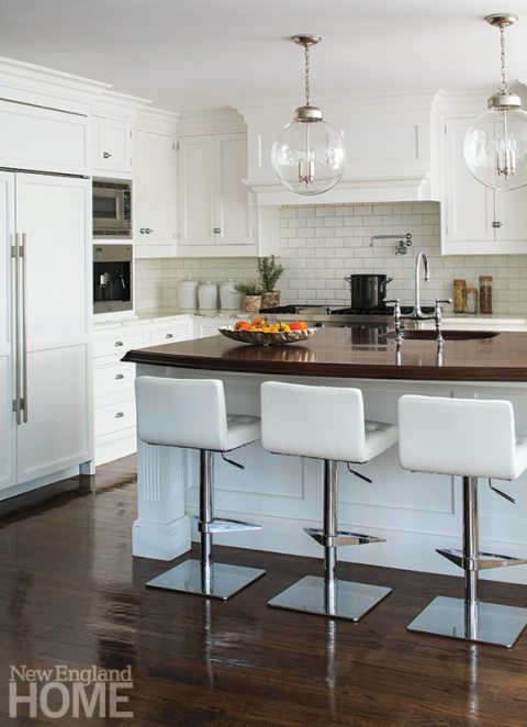 The classic white kitchen was given contemporary touches such as the cabinet hardware, light fixtures, and bar stools.