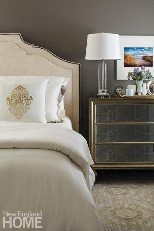 The master bedroom takes a glamorous turn with a nailhead-studded headboard and a mirrored dresser that acts as a nightstand.
