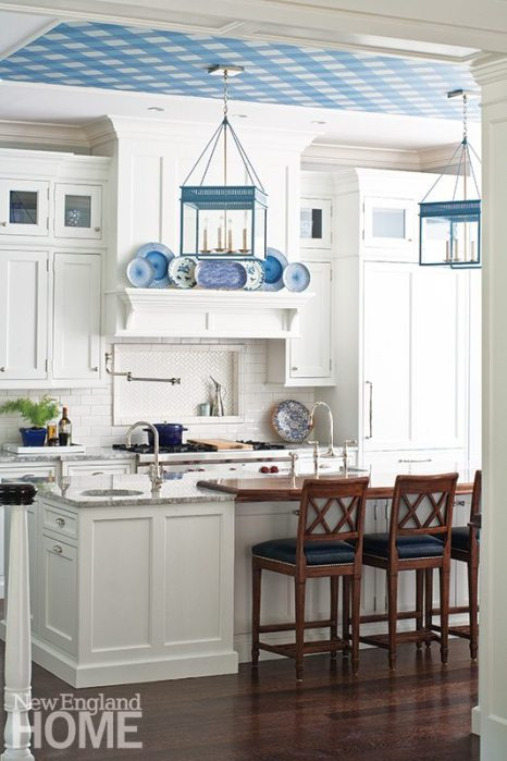"The white-on-white kitchen is punctuated by a judicious use of blue: lanterns, decorative plates, and the room's ""little spark,"" gingham-style wallpaper on the ceiling."