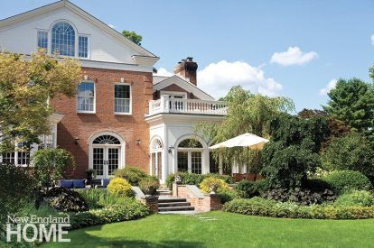 The conservatory opens onto a casual patio and broad lawn.