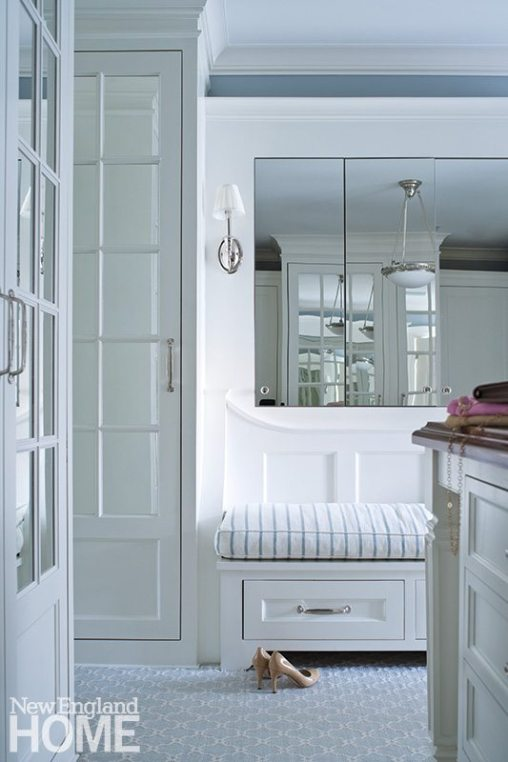 Two walk-in closets were combined to create a dressing room with mirrored cabinetry and a central island with a polished mahogany wood top.
