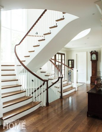 Divided stairs in the entry hall bestow a gracious ambience that befits a medley of family antiques, including a grandfather clock.