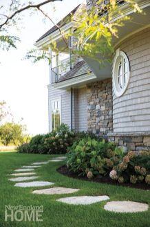 A granite stepping-stone path with a simple perennial border leads to a side entrance.
