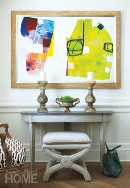 The foyer sets the home's genteel tone with an antique demilune, one of the pair the homeowner and designer Julie Nightingale scored at a French flea market, and an antique Swedish daybed from Circa Antiques in Westport.