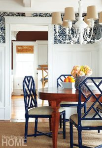 Bright navy lacquer on the dining chairs and a blue-and-white Ralph Lauren wallpaper lend a playful look to the dining room.