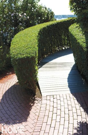 Carefully manicured boxwoods line the path up to the deck.