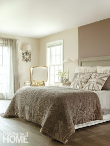A wall painted in Farrow & Ball's London Clay sets off the master bedroom's custom-upholstered bed.