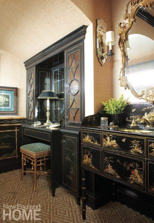 The black-lacquered powder room takes its cues from a chinoiserie painted chest the homeowner found and that interior designer Cindy Rinfret turned into a vanity.