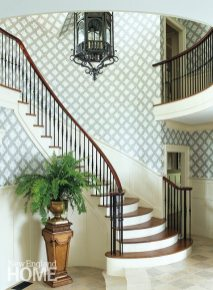 The designers tamed the double-height foyer, bringing warmth and drama with a Cole & Son wallpaper and oversize antique lantern.