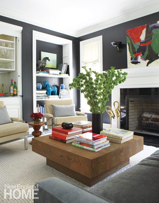 Colorful accessories pop in the living room, where walls of Benjamin Moore's Jet Black set off the crisp white trim and shelves.