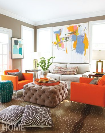 Vintage orange chairs complement Kerri's artwork with a bit of extra punch in the television room. The ottoman is another custom D2 Interieurs design.