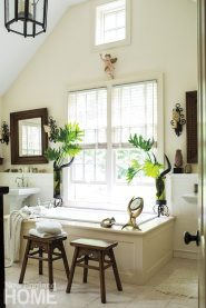 A hand-forged chandelier and sconces by Laura Lee Designs and a cache of shapely animal horns bring another layer of interest to the sunny master bath.