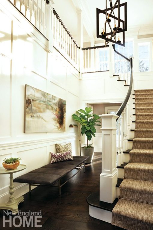 Boxed panels on the entry's walls echo the classic rectangular windows at the top of the stairs. A Bernhardt bench shines beneath the edgy lantern fixture from Lillian August.