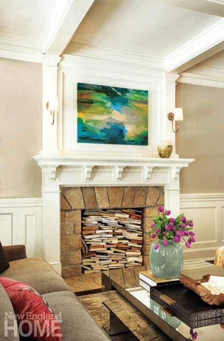 A collection of books fills the fireplace, lending a whimsical touch to the living room.