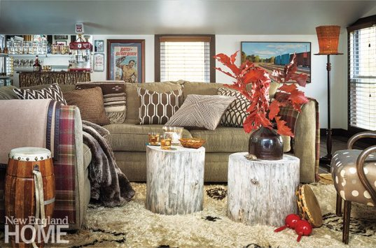 Blankets from Ralph Lauren Home and pillows galore amp up the coziness in the family room; bark removed from the stump tables dresses the bar in the background.