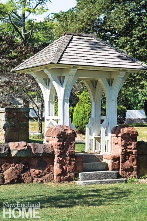 A gazebo with two built-in benches anchors the sandstone wall.