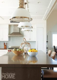 Pendants of milk glass and polished nickel add to the nautical ambience in the kitchen.