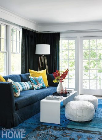 The home's pale color scheme of grays and whites gives way to rich, warm blues in the sitting room.