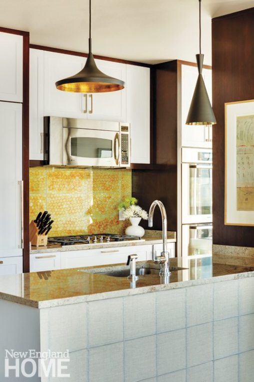 A colorful backsplash from Ann Sacks brightens the kitchen as do the brass pendant lights, with a black patinated exterior, by Tom Dixon.