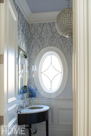 A giant ikat print wallcovering flows around the first-floor powder room's charming oval window.
