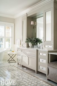 Mirrored drawers and cabinet doors play up the substantial light that spills through the master bathroom windows.