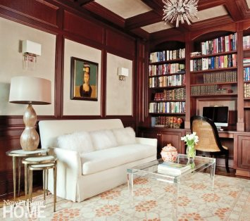 A contemporary chandelier and an acrylic coffee table are fun contemporary notes in the paneled library. The rug adheres to the owner's preference for elements that incorporate warm and cool colors, while the Osborne & Little sofa fabric speaks to the pale suede wall panels.