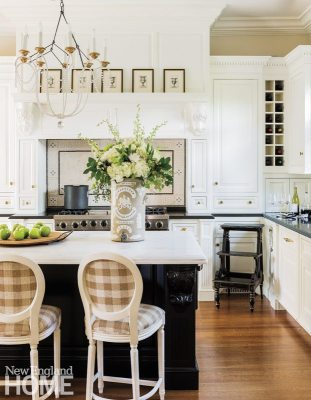 The efficient black-and-white kitchen incorporates an Italian chandelier and wine storage. The old English water filter holding flowers was unearthed at the Brimfield Antique Show and given new purpose.